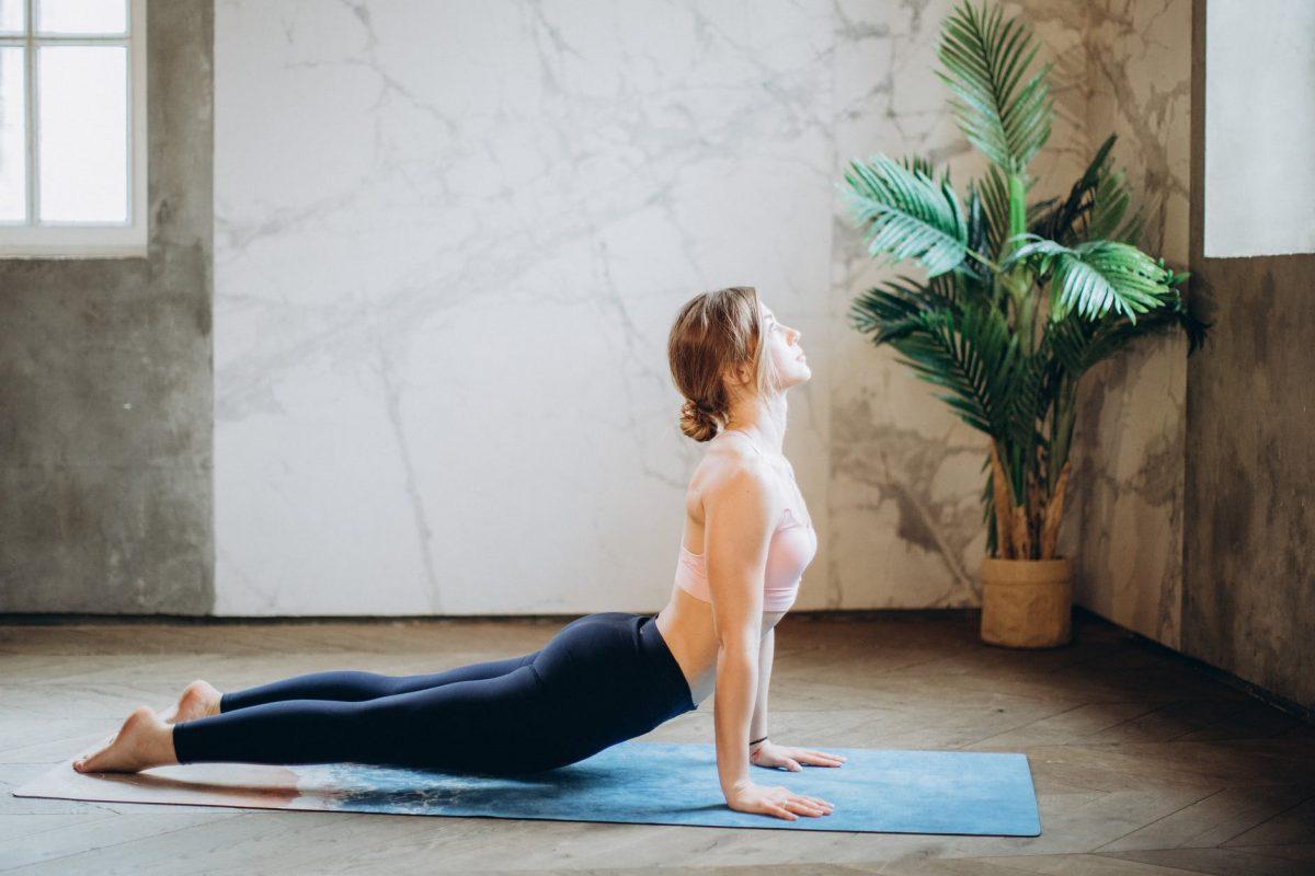 woman in pink sports bra and black leggings doing yoga on yoga mat