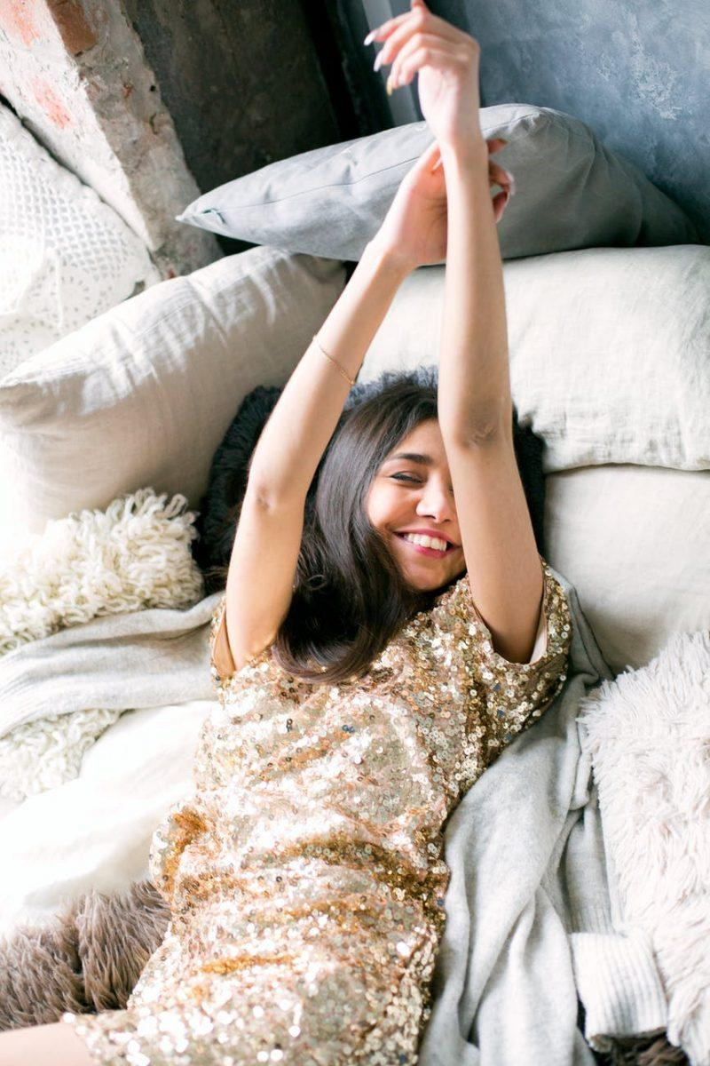 woman wearing brown sequin dress laying on the bed